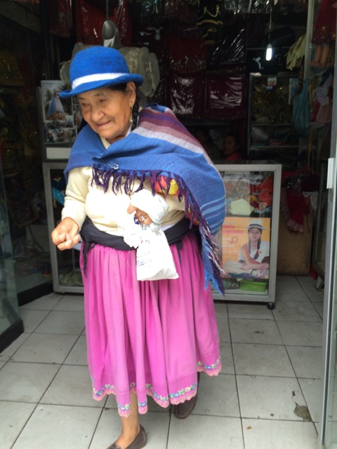 Woman in Cuenca wearing a blue felt hat and traditional full skirt with lace border.