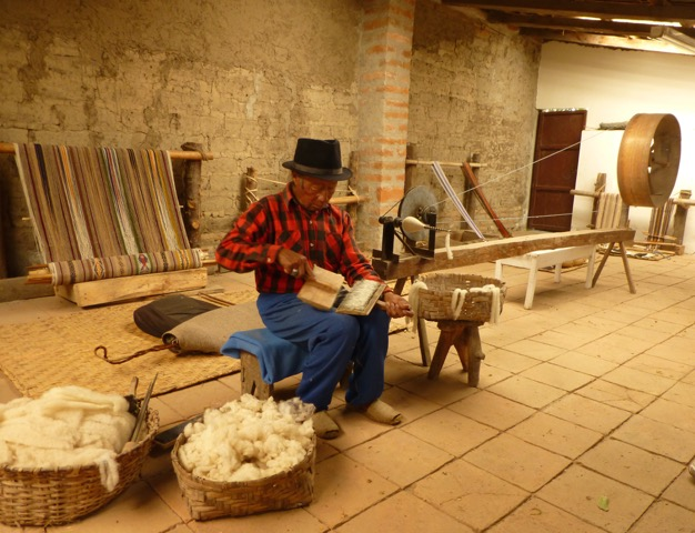 Miguel carding the wool in his new weaving studio. His family no longer work all day at this, but now come here on weekends to continue the tradition of back strap weaving.