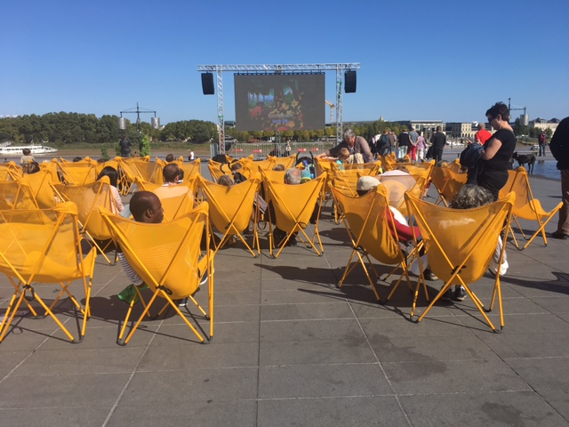 Kids and all ages enjoy a movie in the broad daylight on a warm afternoon on the river bank by the reflecting pool with sprinklers that shoot from the tiled floor.